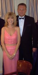 A woman in a beautiful pink wedding dress stands in front of a man in tuxedo