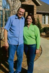 A laughing man wraps his arm around a Texas Christian woman who smiles