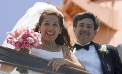 A woman screams with delight as she and her new husband look down from a bridge