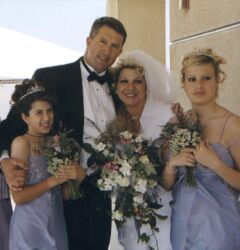 A man hugs his daughter and new wife as blended family are united