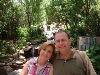 A Christian couple smile and cuddle together near a waterfall