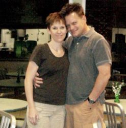 Happily married Christians hug side by side and smile on their anniversary at a restaurant