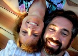 A couple lie upside down smiling