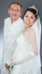 A happy new bride smiles next to her elated husband, both dressed in white