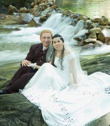 Beautiful shot of Australian and Malaysian Christians sitting by rapids after marrying