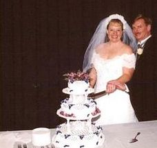 A beaming bride cuts the wedding cake with her groom