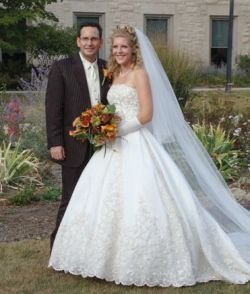 A beautiful woman in a wedding dress with a long veil stands next to her husband and holds her bouquet