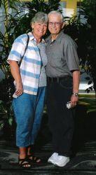 Senior Christians stand hand in hand and cheek to cheek