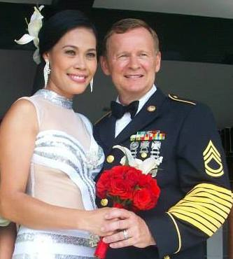 A gorgeous Asian woman holds a red bouquet of flowers while standing next to a good looking White man in military suit