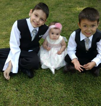 Adorable brothers in suits hug baby sister on grass