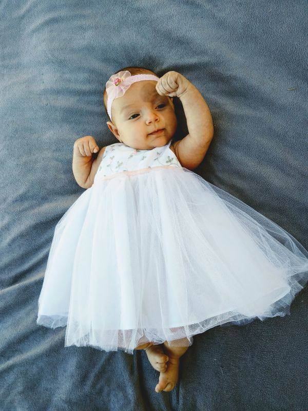 Baby girl in white dress for Christian couple