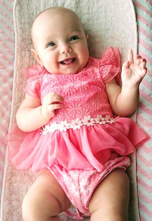 Laughing baby girl in pink lying down