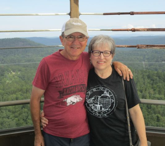 15 years of marital bliss for smiling middle aged Christians who smile while posing over forest lookout