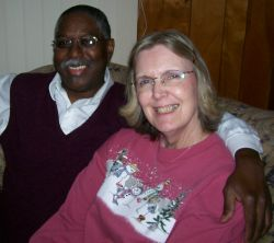 Midwest Christian senior couple sitting together and smiling on the couch