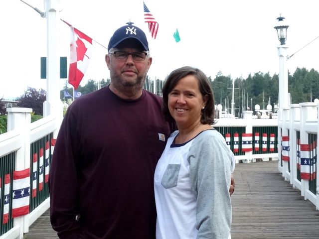 Patriotic flags in background with couple smiling on harbor walkway