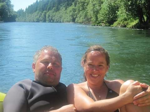 Christian couple smiling and lazing on a boat while floating down the river
