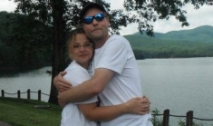 A couple hug outside in front of a beautiful lake