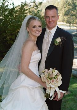 Julie with beautiful wedding dress and flowers stands next to her proud husband