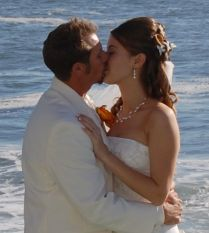 A couple kiss romantically by the ocean after marrying