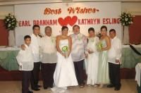 Wedding party flank newlyweds who stand under joined hearts