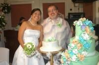 Newlyweds burst out laughing while trying to pose in front of their Wedding cake