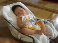 A sleeping baby body in his carseat