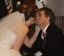 A new Christian bride holds her husband's face while kissing him tenderly