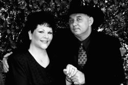 A Christian man in a cowboy hat holds hands with a pretty woman dressed in black