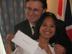 A jubilant interracial couple shows off proof of marriage