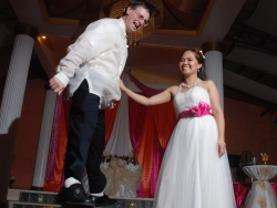 A man dances precariously on a table while his laughter wife cheers him on