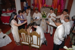 Couples pray together over a bride and groom who sit with bowed heads
