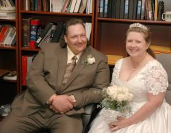 A seated couple look very relaxed and pleased on their wedding day