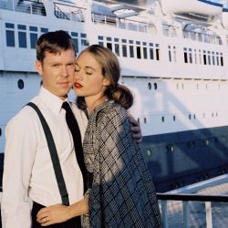 A beautiful woman leans in and hugs a handsome man next to a cruise ship
