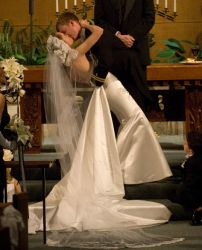A man leans his wife over for a kiss at the altar