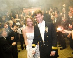 A couple nearly doubled over with laughter at their wedding reception
