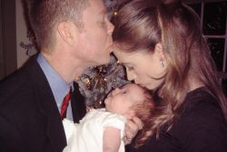 A loving husband kisses his wife's forehead as she kisses the baby they're holding