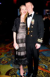 A well dressed couple pose together at a ball