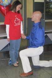 A man proposes on one knee to a woman wearing a Team Canada Jersey