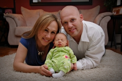 Beautiful parents proudly hold their sleeping baby while lying on a rug