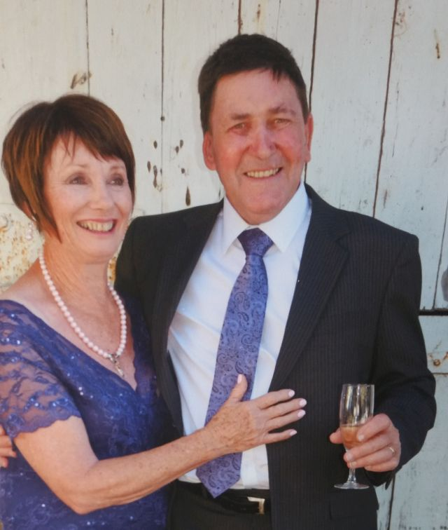New Zealand Christian man telling a joke while his hugging wife laughs