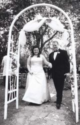 Beautiful archway frames this black and white photo of a married couple walking hand in hand