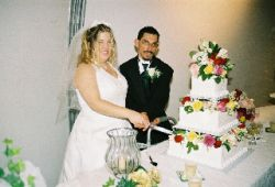 A bride laughs as her husband helps her cut the wedding cake