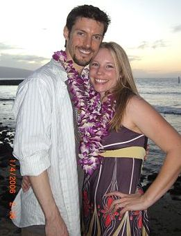 Christian biker engaged in Hawaii stands next to his new fiancee on the beach