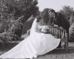 Christian man leans over a bench and talks to his pretty bride in a beautiful dress