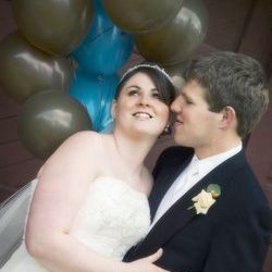 Groom whispers in his wife's ear as she smiles on their wedding day