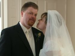 A bride tries to sneak a kiss while the groom is distracted