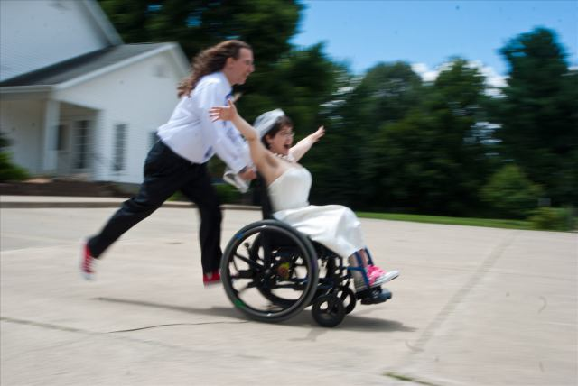 Man pushes woman quickly in wheelchair as she screams in laughter