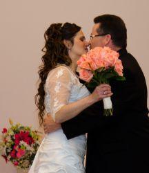 A romantic Christian couple lovingly kiss at their wedding