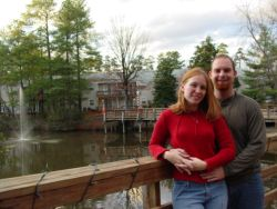 Attractive Christian singles stand close together on a bridge and look very happy