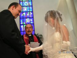 Woman in veil holds holds her husband's hands at their wedding ceremony